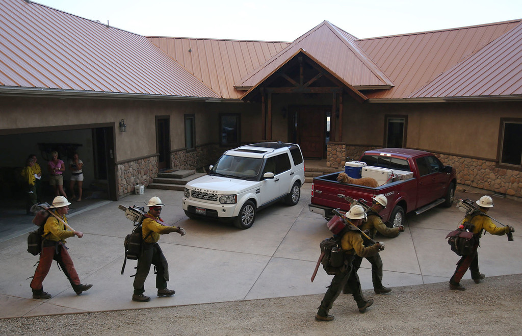 . Members of the Ironwood Hotshots from Tucson, Ariz.,   walk by a home in PIne, Idaho,  Sunday, Aug. 11, 2013, as help fight the 80,300-acre Elk Complex fire burning across Elmore County   The hotshots were clearing a defense area around the home.   (AP Photo/The Times-News,  Ashley Smith)