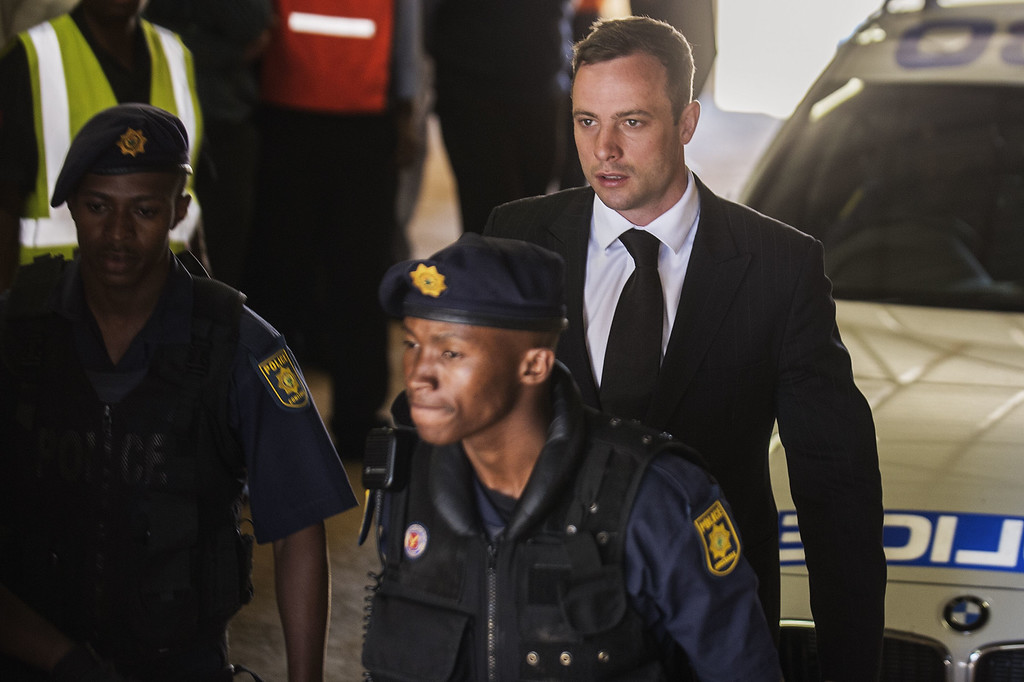 . South African Paralympian athlete Oscar Pistorius (C) is escorted to a police vehicle to be transported to prison following his sentencing at the High Court in Pretoria, on October 21, 2014. AFP PHOTO/GIANLUIGI GUERCIA/AFP/Getty Images