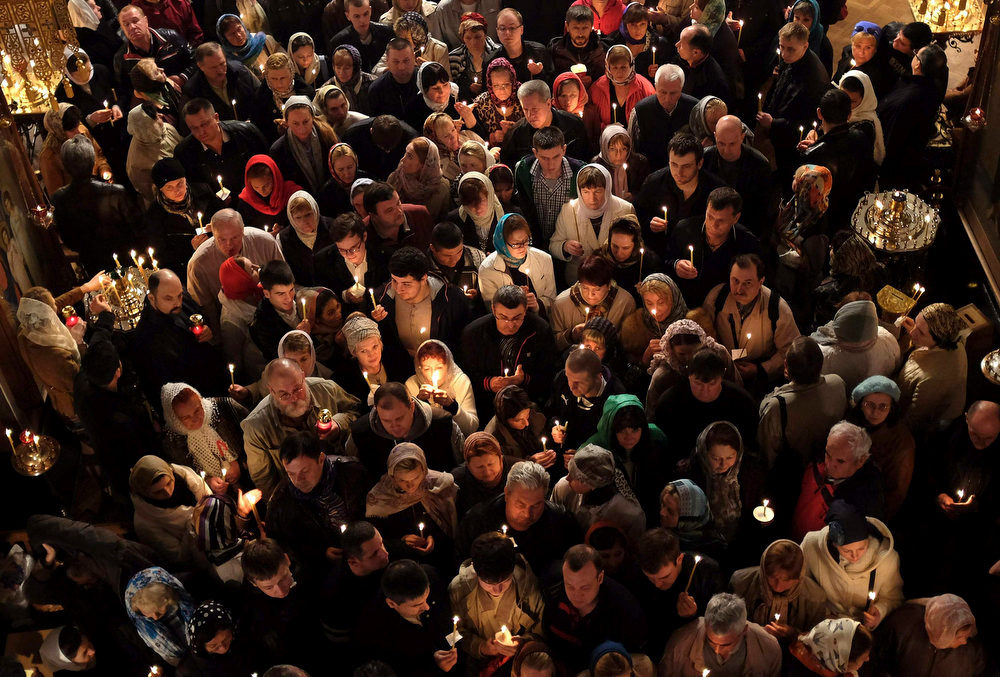 . Russian Christian Orthodox worshippers hold candles during a holy Easter service at the Church of St. Peter and Paul in Karlovy Vary May 5, 2013. The spa town of Karlovy Vary has a large number of Russian residents and is also a popular tourist destination for visitors from Russia.    REUTERS/David W Cerny