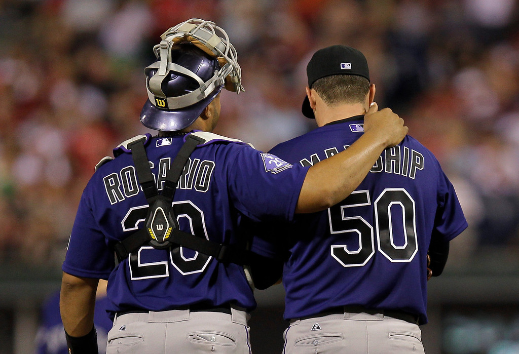 . Colorado Rockies pitcher Jeff Manship talks with catcher Willin Rosario after loading the bases in a baseball game against the Philadelphia Phillies, Monday, Aug. 19, 2013, in Philadelphia. (AP Photo/Laurence Kesterson)