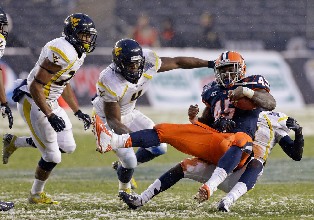 Description of . West Virginia linebacker Josh Francis (4) watches as cornerback Pat Miller, right rear, brings down Syracuse running back Jerome Smith (45) during the first half of the Pinstripe Bowl NCAA college football game at Yankee Stadium in New York, Saturday, Dec. 29, 2012. (AP Photo/Kathy Willens)