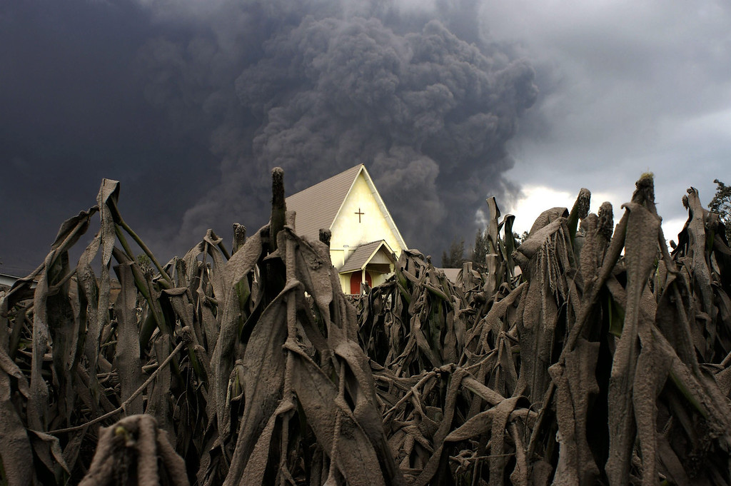 . A church is seen in the middle of a corn field covered with volcanic ash as Mount Sinabung spews volcanic materials as seen from Sibintun village in Karo, North Sumatra, Indonesia, on Jan. 6, 2014. More then 20,000 people have been displaced since the volcano began its most recent activity in September, officials said.  EPA/MAFA YULI RAMADHANI
