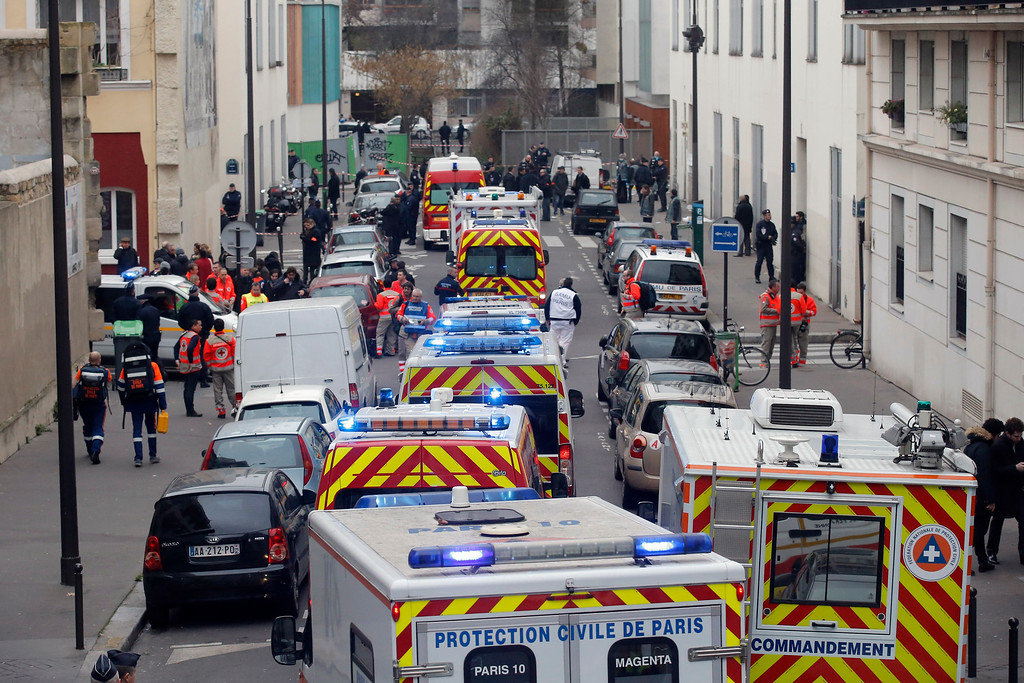 . Ambulances gather in the street outside the French satirical newspaper Charlie Hebdo\'s office, in Paris, Wednesday, Jan. 7, 2015. Masked gunmen stormed the offices of a French satirical newspaper Wednesday, killing at least 11 people before escaping, police and a witness said. The weekly has previously drawn condemnation from Muslims.  (AP Photo/Francois Mori)