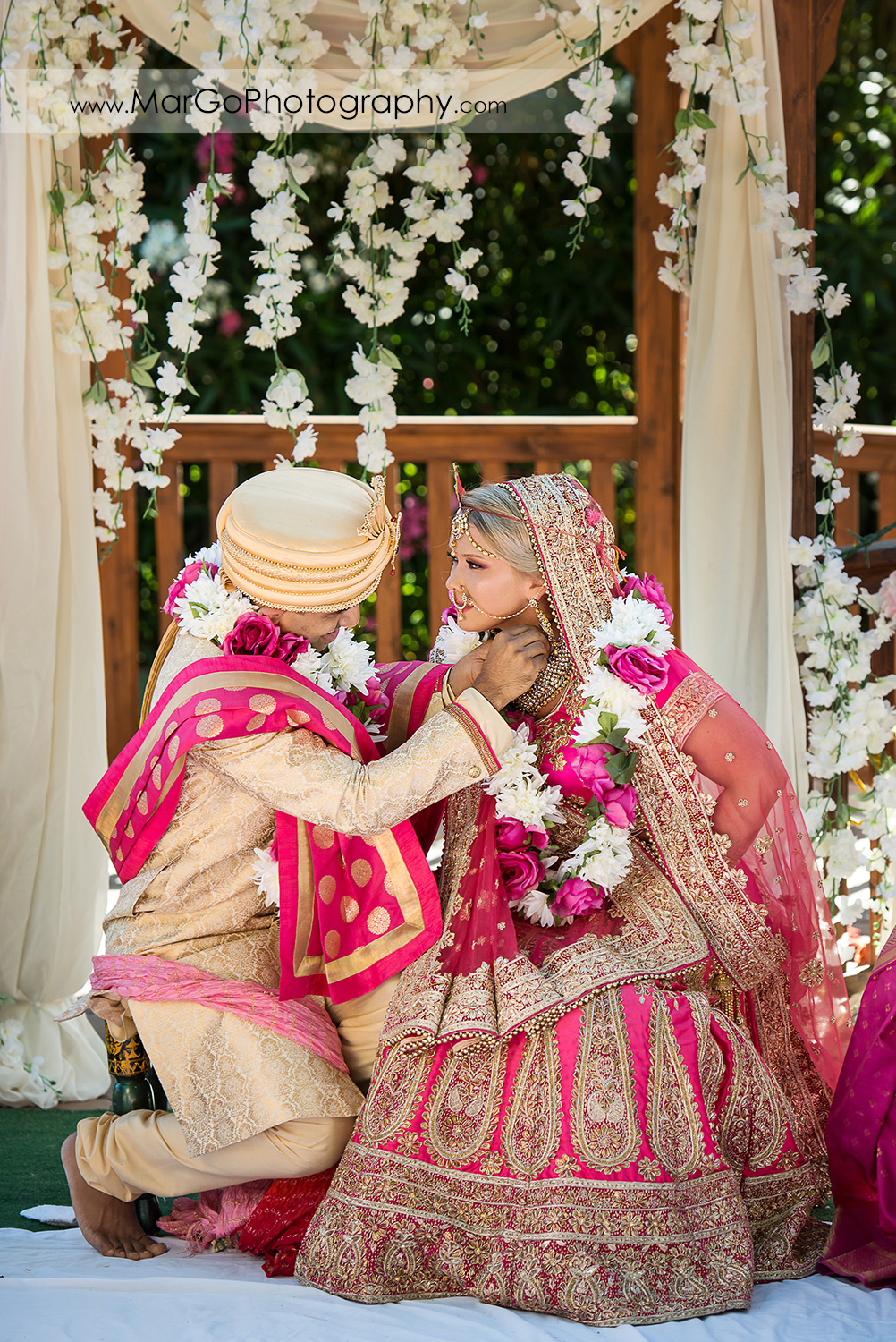 Indian groom adorns the bride with a necklace Mangalsutra under Mandap during wedding ceremony at Elliston Vineyards in Sunol