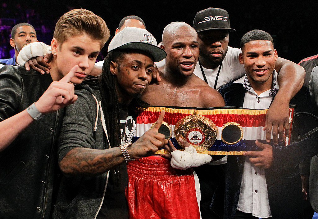 . Floyd Mayweather Jr., center, poses for a photo with, from left, Justin Bieber, Lil\' Wayne, 50 Cent and Cuban boxer Yuriyorkis Gamboa after defeating Miguel Cotto for the WBA super welterweight title, Saturday, May 5, 2012, in Las Vegas. (AP Photo/Eric Jamison)