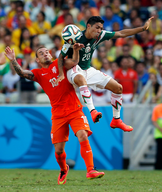 . Netherlands\' Wesley Sneijder, left, and Mexico\'s Javier Aquino battle for the ball during the World Cup round of 16 soccer match between the Netherlands and Mexico at the Arena Castelao in Fortaleza, Brazil, Sunday, June 29, 2014. (AP Photo/Wong Maye-E)