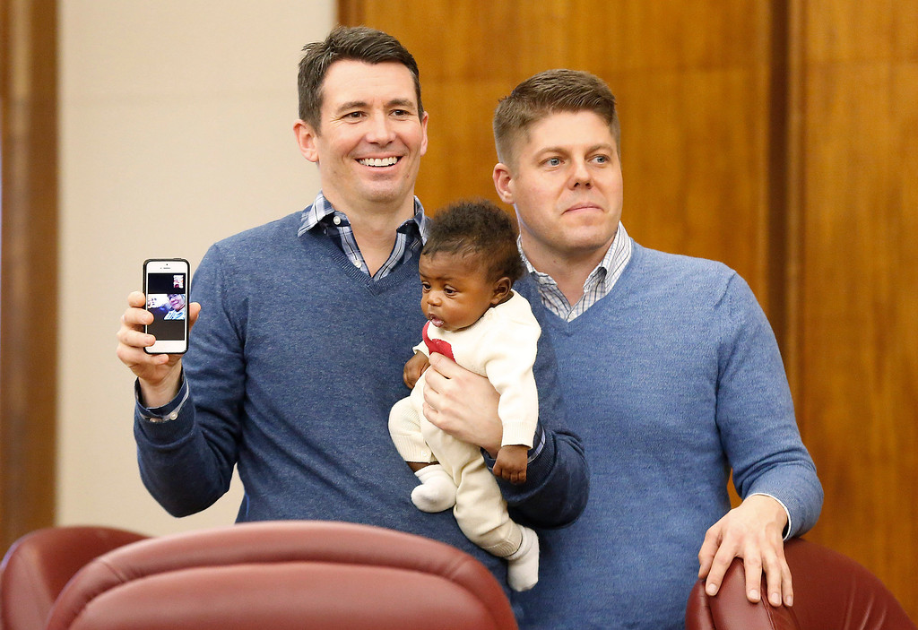 . Jim, left, and Jason Shaffer, hold their daughter Norah, 3 mo., while being married in a group by the Oakland County Clerk in Pontiac, Mich., Saturday, March 22, 2014. A federal judge has struck down Michigan\'s ban on gay marriage Friday the latest in a series of decisions overturning similar laws across the U.S. Some counties plan to issue marriage licenses to same-sex couples Saturday, less than 24 hours after a judge overturned Michigan\'s ban on gay marriage. (AP Photo/Paul Sancya)