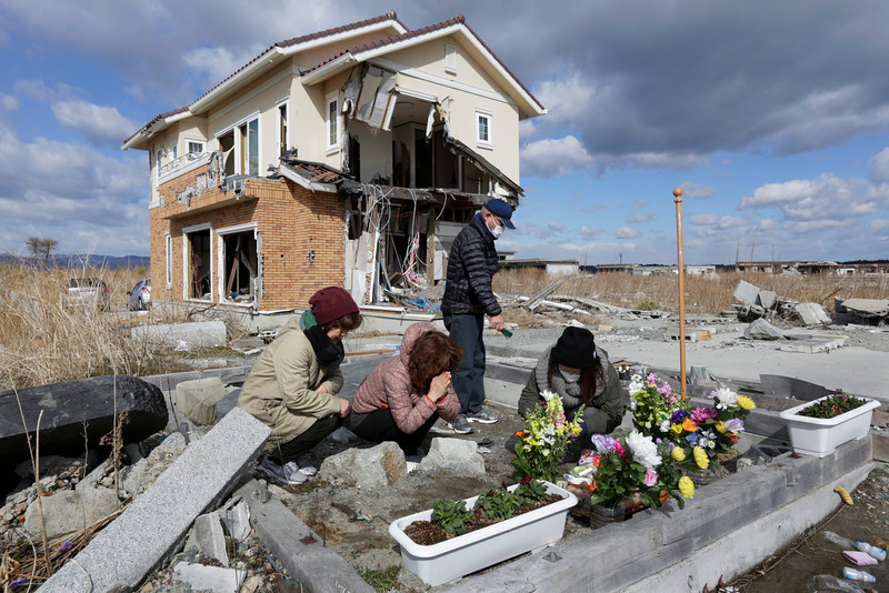 . Chiyoko Hirata (2-L) offers a prayer for her parents Choji and Yoriko Suzuki with her elder sister Hisako Matsuda (L) on the remain of her parents\' home living room in front of her house destroyed in the tsunami-devastated Ukedo area in entry-restricted town of Namie, Fukushima Prefecture, northern Japan, five kilometers north of Tokyo Electric Power Co.\'s Fukushima Daiichi Nuclear Power Plant, 11 March 2014. A 9.0 magnitude earthquake on 11 March 2011 struck off the coast of Japan followed by a tsunami that triggered the nation\'s worst nuclear accident at Fukushima Daiichi Nuclear Power Plant in nearby Fukushima. The disaster left about 19,000 people dead and missing.  (EPA/KIMIMASA MAYAMA)
