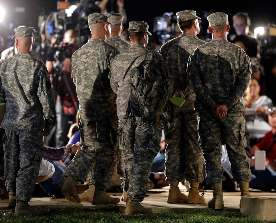 . Soldiers listen in the wings as Lt. Gen. Mark Milley address the media during a news conference at the main gate to Fort Hood, Wednesday, April 2, 2014, in Fort Hood, Texas. (AP Photo/Eric Gay)