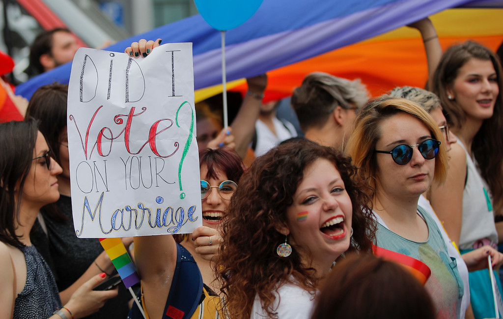 """. Participants, one holding a banner that reads \""""Did I vote on your marriage?\"""" react, during a gay pride parade in Bucharest, Romania, Saturday, June 9, 2018. People taking part in the gay pride parade in the Romanian capital demanded more rights and acceptance for same-sex couples.(AP Photo/Vadim Ghirda)"""