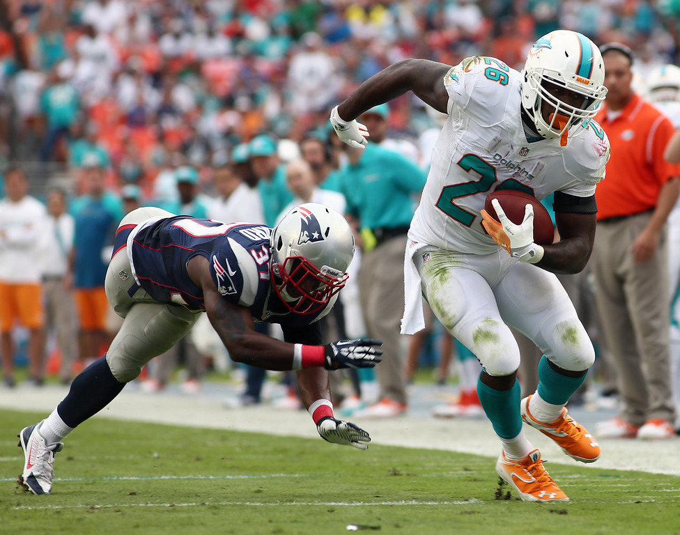 . Miami Dolphins running back Lamar Miller (26) gets away from a tackle by New England Patriots cornerback Alfonzo Dennard, left, during the second half of an NFL football game, Sunday, Dec. 15, 2013, in Miami Gardens, Fla. (AP Photo/J Pat Carter)