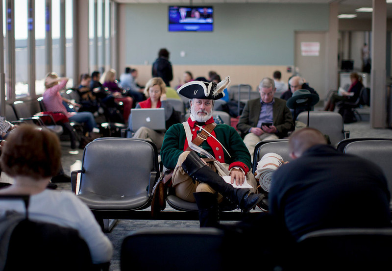 . In this Wednesday, Jan. 4, 2012 file photo, tea party supporter William Temple, of Brunswick, Ga., dressed in a Revolutionary War-era military uniform sits in the Des Moines Airport waiting to fly home after the Iowa caucus in Des Moines, Iowa. (AP Photo/Evan Vucci)
