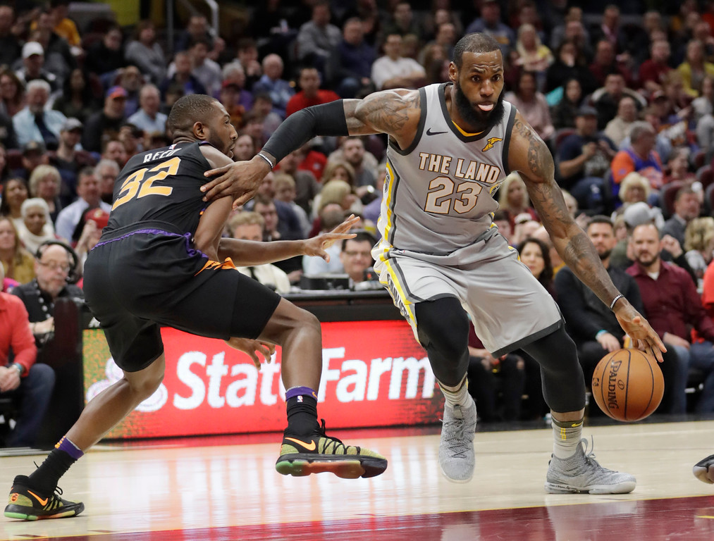 . Cleveland Cavaliers\' LeBron James (23) drives past Phoenix Suns\' Davon Reed (32) in the second half of an NBA basketball game, Friday, March 23, 2018, in Cleveland. (AP Photo/Tony Dejak)