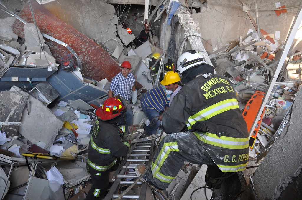 . Firefighters belonging to the Tacubaya sector and workers dig for survivors after an explosion at an adjacent building to the executive tower of Mexico\'s state-owned oil company PEMEX, in Mexico City, Thursday Jan. 31, 2013. A large explosion occurred in the lower floors of the building and dozens have been reported injured so far. (AP Photo/Guillermo Gutierrez)
