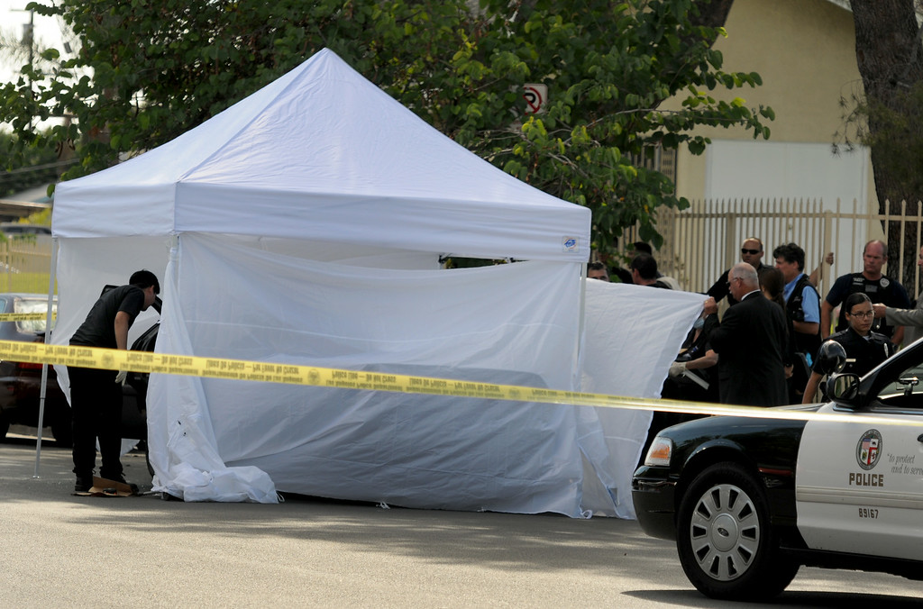 . Los Angeles Police Department officers investigate the scene of a shooting where one person was killed in the 12900 block of Filmore Street in Pacoima, CA on August 24, 2014.  Describing what they called �a major public threat,� Los Angeles police said they are seeking clues to three separate shootings in the Northeast San Fernando Valley that left three people dead and four others injured early Sunday morning and appear to be connected. The three incidents, which were described as having �a similar manner,� took place between 5:50 and 6:45 a.m. Sunday in the city of San Fernando and in the Los Angeles communities of Sylmar and Pacoima, Los Angeles Police Department officials said. (Photo by Dean Musgrove/Los Angeles Daily News)