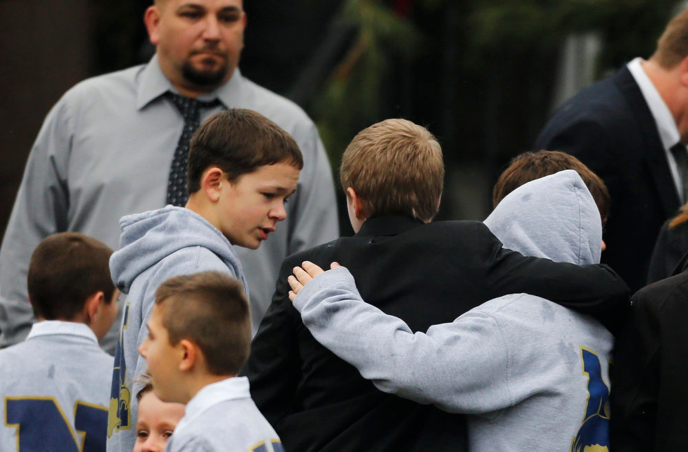 Description of . Students embrace while wearing Newtown school shirts outside the funeral for six-year-old student shooting victim Jack Pinto in Newtown, Conn., Monday, Dec. 17, 2012. A gunman opened fire at Sandy Hook Elementary School in the town on Friday, killing 26 people, including 20 children before killing himself. (AP Photo/Charles Krupa)