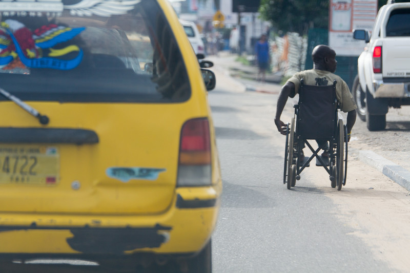 Monrovia, Liberia October 13, 2017 - A man pushes his wheel chair through traffic.