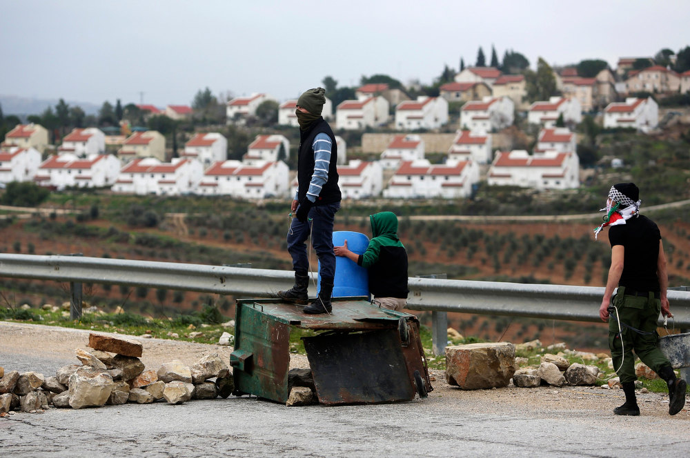 . The Jewish settlement of Halamish is seen in the background as a stone-throwing Palestinian protester stands on a garbage bin during clashes with Israeli security officers at a weekly protest against the settlements, in the West Bank village of Nabi Saleh, near Ramallah February 1, 2013. U.N. human rights investigators called on Israel on Thursday to halt settlement expansion and withdraw all half a million Jewish settlers from the occupied West Bank, saying that its practices could be subject to prosecution as possible war crimes. REUTERS/Mohamad Torokman