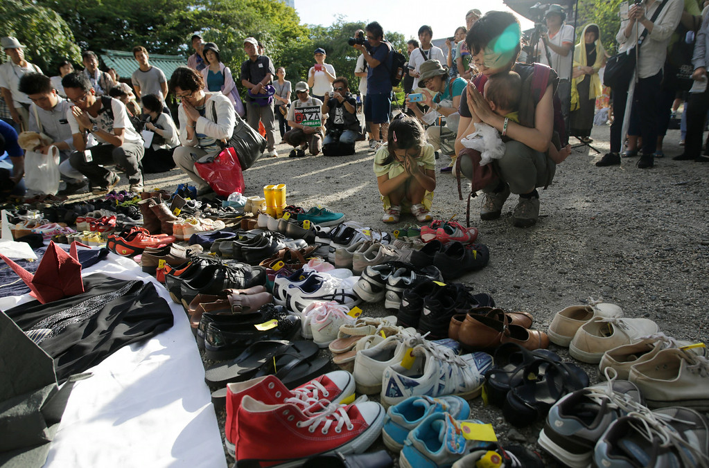 . People pray after placing shoes symbolizing the war dead of children in Gaza, at Zojyoji Buddhist Temple in Tokyo Saturday, Aug. 23, 2014. Since the war erupted July 8, more than 2,090 Palestinians have been killed, including close to 500 children, and about 100,000 Gazans have been left homeless, according to United Nations figures and Palestinian officials. Israel lost 64 soldiers and four civilians, including a 4-year-old boy killed by a mortar shell Friday. (AP Photo/Eugene Hoshiko)