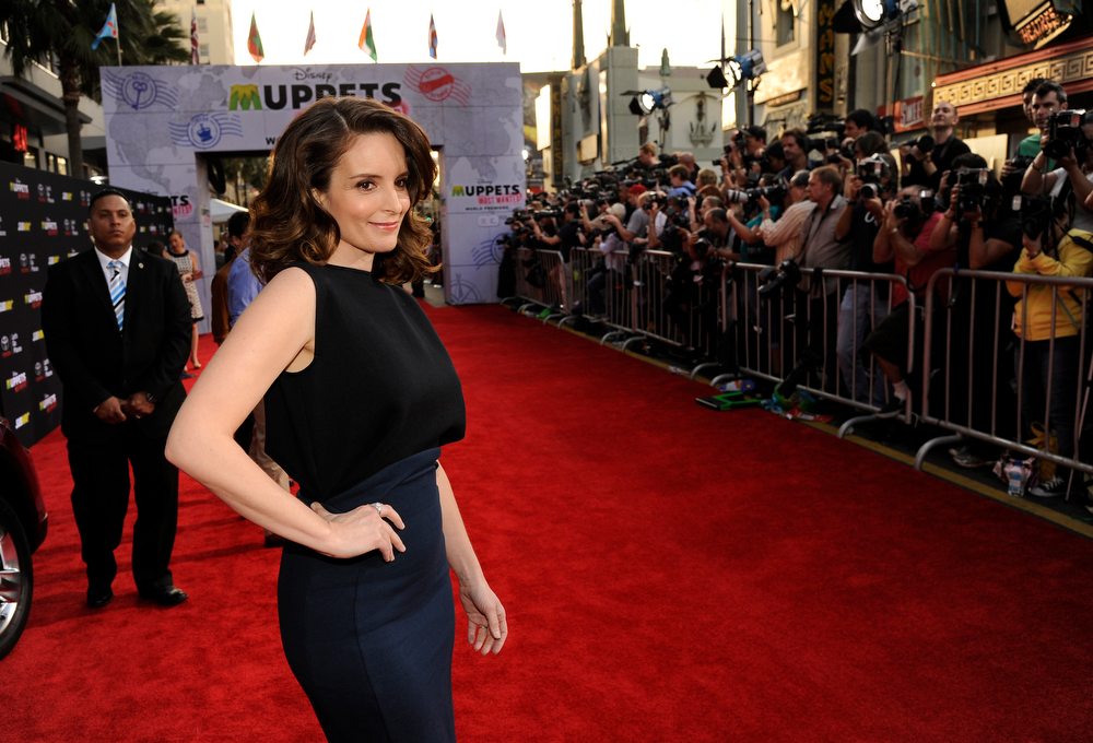 """. Tina Fey, a cast member in \""""Muppets Most Wanted,\"""" poses on the red carpet at the premiere of the film on Tuesday, March 11, 2014, in Los Angeles. (Photo by Chris Pizzello/Invision/AP)"""