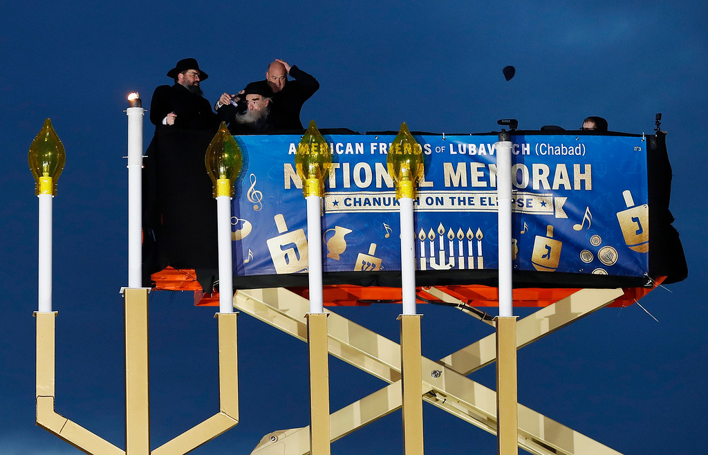 . National economics adviser Gary Cohn, right, reacts as his yarmulke is blown by wind from his head as Rabbi Levi Shemtov, left and Rabbi Abraham Shemtov stand with him in a scissor lift to light the Menorah during the annual National Menorah Lighting, in celebration of Hanukkah, on the Ellipse near the White House in Washington, Tuesday, Dec. 12, 2017. (AP Photo/Carolyn Kaster)