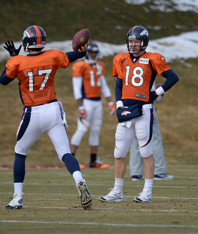 . Denver Broncos quarterback Peyton Manning (18) watches Denver Broncos quarterback Brock Osweiler (17) throw a pass during practice January 15, 2014 at Dove Valley. The Broncos are preparing for their game against the New England Patriots in the AFC championship game.  (Photo by John Leyba/The Denver Post)