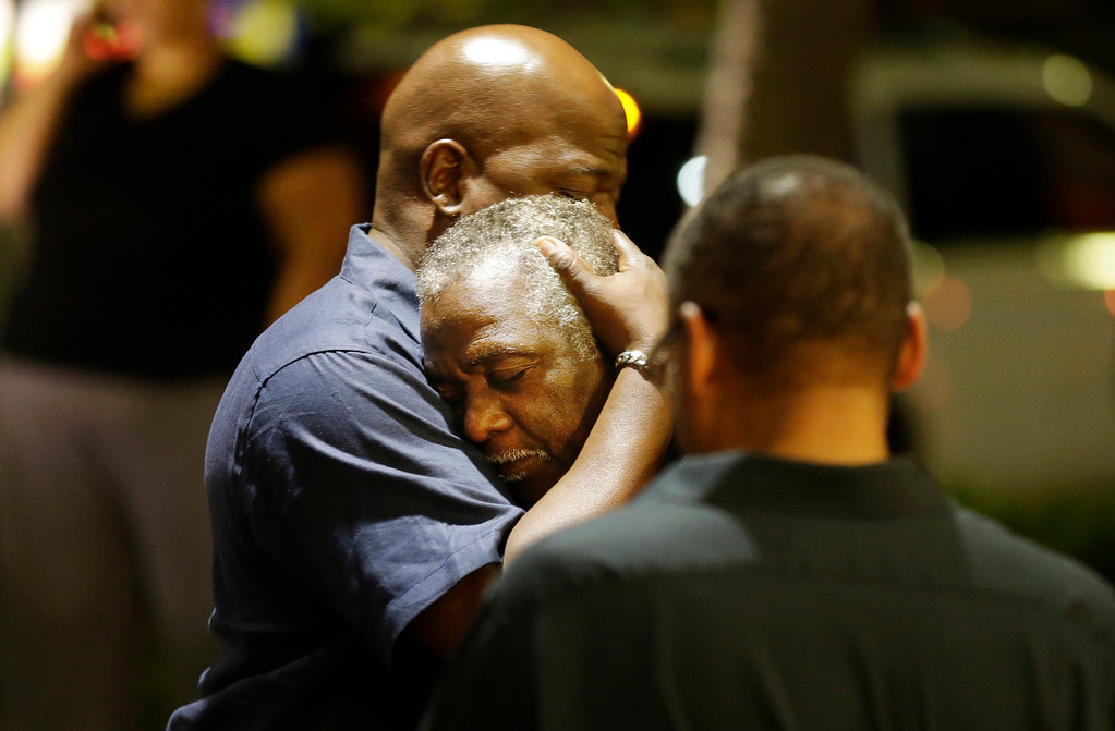 . Worshippers embrace following a group prayer across the street from the scene of a shooting Wednesday, June 17, 2015, in Charleston, S.C. (AP Photo/David Goldman)