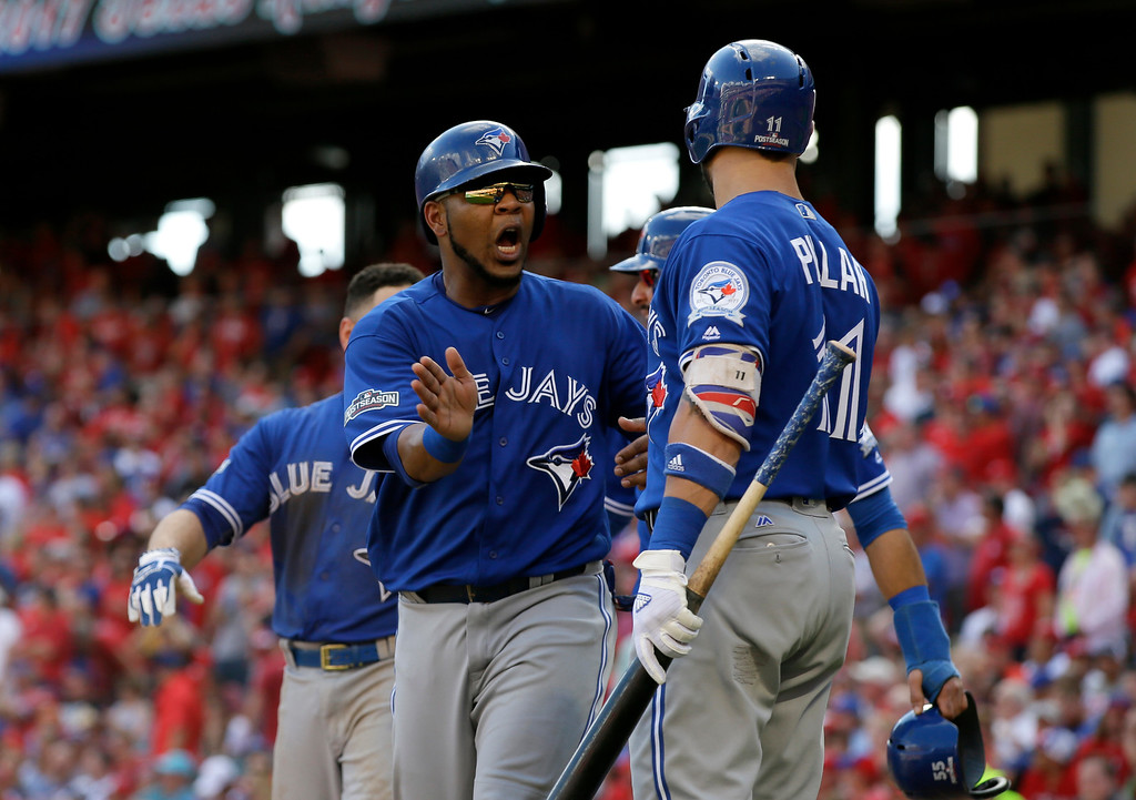 . Toronto Blue Jays\' Edwin Encarnacion celebrates with Kevin Pillar (11) after scoring on a bases-clearing triple by Troy Tulowitzki in the third inning of baseball Game 1 of the American League Division Series against the Texas Rangers on Thursday, Oct. 6, 2016, in Arlington, Texas. (AP Photo/LM Otero)