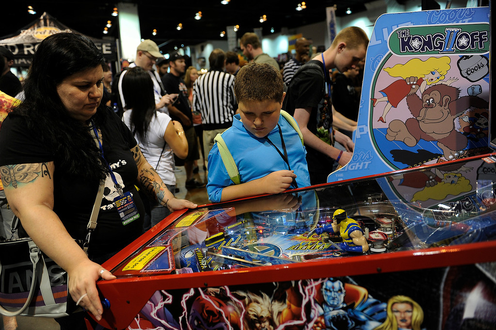 . DENVER, CO - JUNE 1: Taber Thompson, 9, watches as his mother, Rochelle, plays an Avengers themed pinball game during Denver Comic Con at the Colorado Convention Center on June 1, 2013 in Denver, Colorado. (Photo by Seth McConnell/The Denver Post)