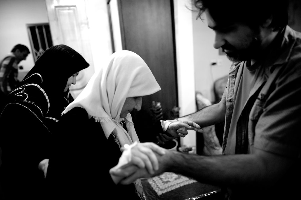 . Soheila Mehri, who suffers from breast cancer, gets help from her brother Hamed (R) and sister-in-law Farahnaz (L) to walk in her house in Tehran on February 25, 2013, when she was feeling better and was able to walk again.  AFP PHOTO/BEHROUZ MEHRI