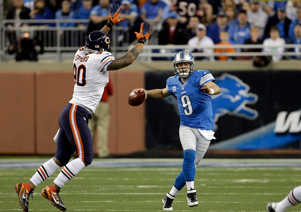 . Detroit Lions quarterback Matthew Stafford (9) looks downfield while chased by Chicago Bears defensive end Julius Peppers (90) during the first quarter of an NFL football game at Ford Field in Detroit, Sunday, Dec. 30, 2012. (AP Photo/Carlos Osorio)