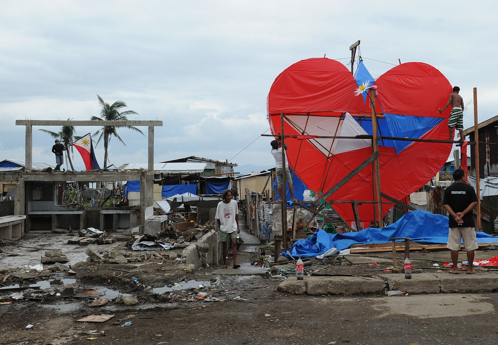 . Residents and survivors of super Typhoon-Haiyan put the finishing touches on a giant heart-shaped lantern displayed along the coastal area of Tacloban City, Leyte province, in central Philippines on February 14, 2014, ahead of the one hundred days anniversary of the devastating super Typhoon that hit the city on November 8, 2013. England football legend David Beckham flew to the Philippines on February 13 to give comfort to survivors of the Asian country\'s deadliest ever typhoon.  AFP PHOTO/TED ALJIBE/AFP/Getty Images