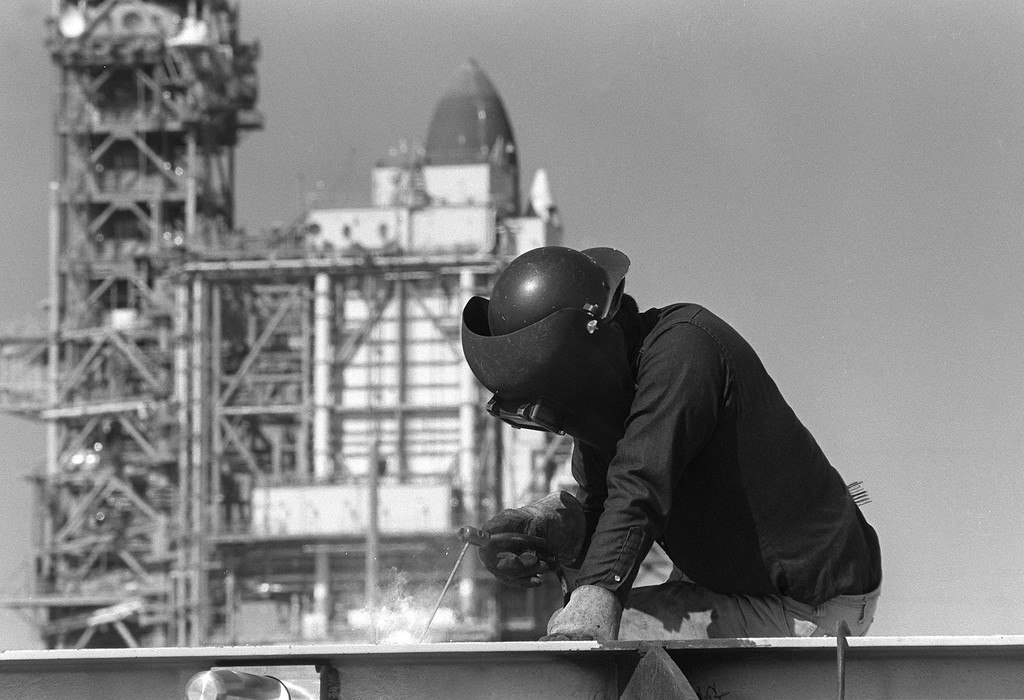 . With the space shuttle Challenger sitting in the backround, a Boeing worker welds a weather shield at Kennedy Space Center\'s Pad 39-B on Jan. 22, 1986.  Six days later the Challenger exploded shortly after launch, killing all seven crew members.  (AP Photo/Phil Sandlin)