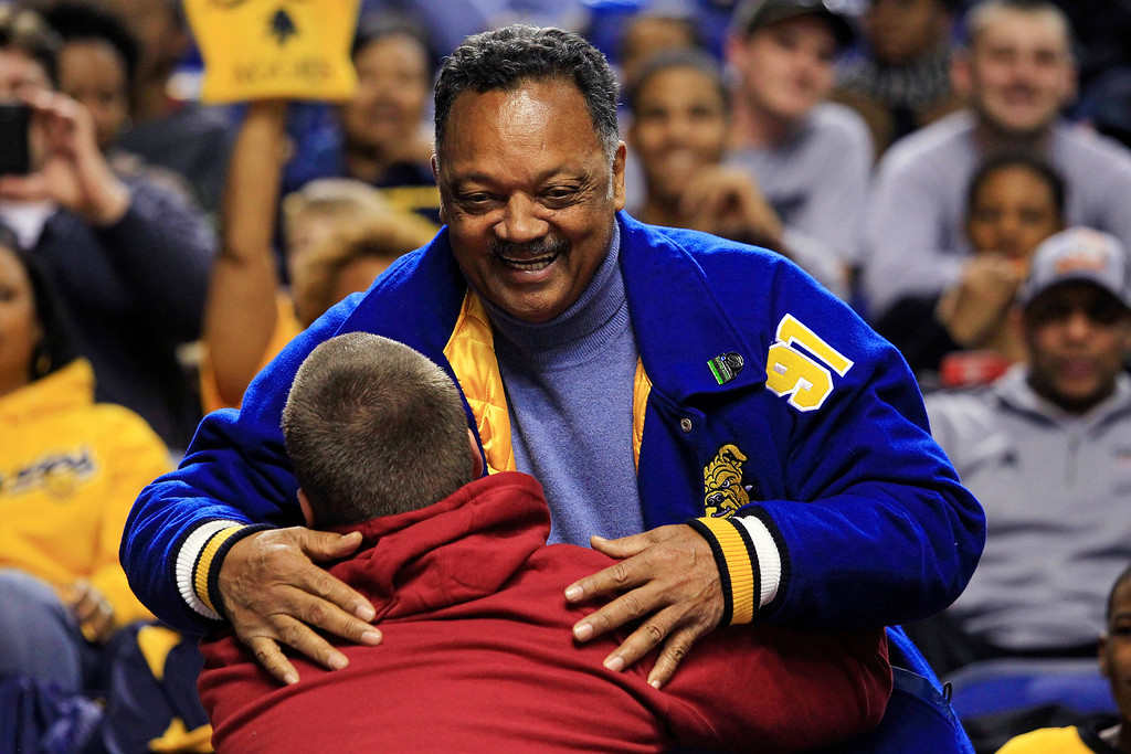 . The Rev. Jesse Jackson embraces an unidentified man before the start of a second-round NCAA college basketball tournament game between Louisville and North Carolina A&T, Thursday, March 21, 2013, in Lexington, Ky. (AP Photo/James Crisp)