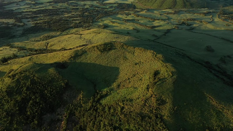 Available in 4K - Aerial image of typical green volcanic caldera crater landscape with volcano cones of Planalto da Achada central plateau of Ilha do Pico Island, Azores