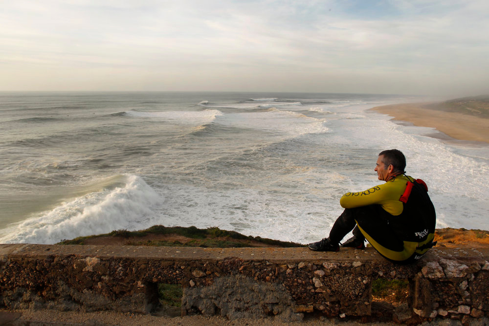 Description of . US surfer Garrett McNamara rests after a surf session at Praia do Norte beach in Nazare, Portugal, Tuesday, Jan. 29, 2013. McNamara is said to have broken his own world record for the largest wave surfed when he caught a wave reported to be around 100ft off the coast of Nazare on Monday. If the claims are verified, it will mean that McNamara has beaten his previous record, which was also set at Nazare, of 78 feet in November 2011. (AP Photo/Francisco Seco)