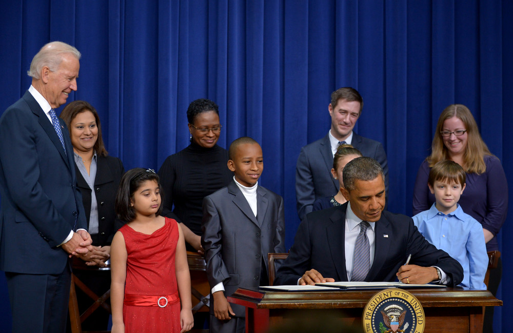 Description of . US President Barack Obama signs executive actions to curb gun violence as Vice President Joe Biden(L) and invited guests look on January 16, 2013 in the South Court Auditorium of the Eisenhower Executive Office Building, next to the White House in Washington, DC. President Obama Wednesday signed 23 executive actions to curb gun violence and demand Congress pass an assault weapons ban and other sweeping measures in response to the Newtown massacre. A senior official also said Obama would call on Congress to pass deeper measures, including bans on high-capacity magazine clips of more than 10 rounds and to prohibit armor-piercing bullets. AFP PHOTO/Mandel  NGAN/AFP/Getty Images