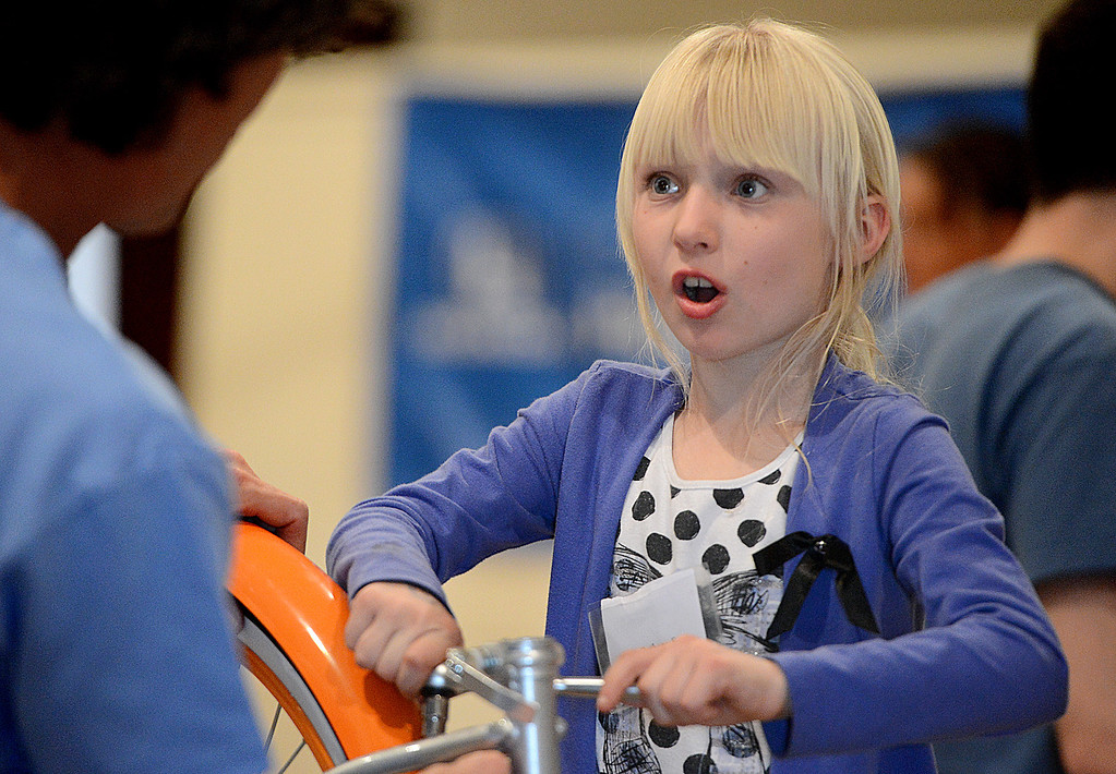 . Bethany Stringer, 9, of Grand Terrace helps assemble her new bicycle. Southern California Honda Dealers� Helpful Guys in Blue hosted a Santa�s Workshop Monday December 16, 2013 building bicycles for children of the Westside Kinship Support Program at St Paul\'s Methodist Church. There was also cookie decorating, face painting, and a visit from Pedals the Clown. The Westside Kinship Support Program is a support system for caregivers who step in to raise extended family members� children who have been separated from or who have lost their parents.