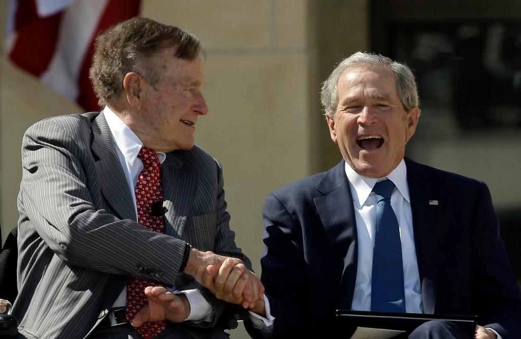 . Former President George H.W. Bush shakes hands with his son, former President George W. Bush during the dedication of the George W. Bush Presidential Center, Thursday, April 25, 2013, in Dallas. (AP Photo/David J. Phillip)