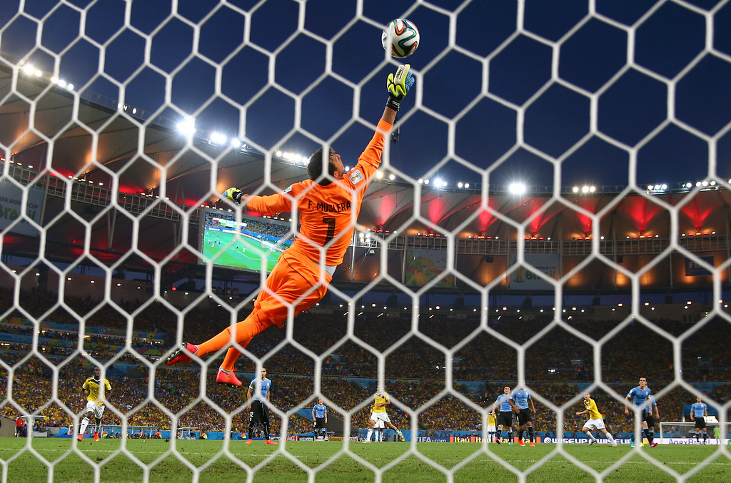. RIO DE JANEIRO, BRAZIL - JUNE 28: James Rodriguez of Colombia scores his team\'s first goal past Fernando Muslera of Uruguay during the 2014 FIFA World Cup Brazil round of 16 match between Colombia and Uruguay at Maracana on June 28, 2014 in Rio de Janeiro, Brazil.  (Photo by Julian Finney/Getty Images)