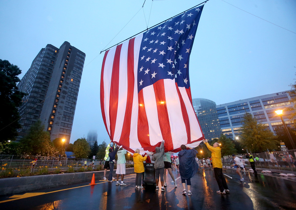 . Volunteers hoist up the U.S. flag at the starting line before the start of the 44th running of the AJC Peachtree Road Race at Lenox Square Thursday morning in Atlanta, Ga., July 4, 2013.  The 10K race is a Fourth of July tradition in Atlanta that\'s billed as the largest road race in the U.S.  (AP Photo/Atlanta Journal-Constitution,Jason Getz )