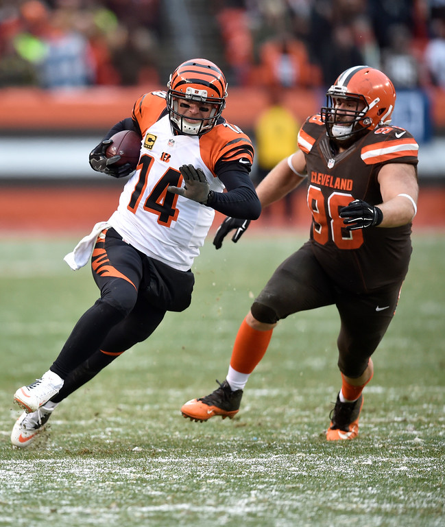 . Cincinnati Bengals quarterback Andy Dalton (14) scrambles as Cleveland Browns defensive end Jamie Meder (98) runs after him in the second half of an NFL football game, Sunday, Dec. 11, 2016, in Cleveland. (AP Photo/David Richard)