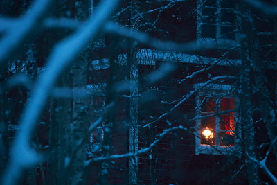 Cottage in wintry forest with lighted window