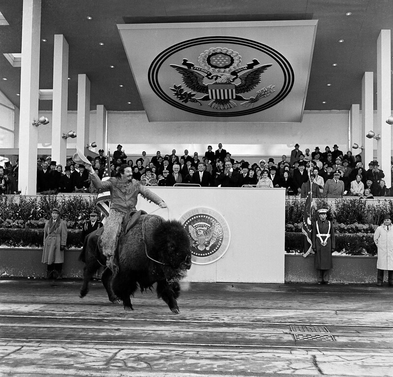 . A man rides a buffalo and draws laughter and applause from spectators in the Presidential reviewing stands, January 20, 1961 in Washinton, D.C. Lyndon Johnson, new Vice-president is seen clapping his hands. President Kennedy\'s father, Joseph P. Kennedy, stands beside him. (AP Photo)