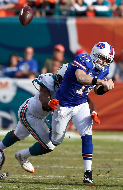 . Buffalo Bills quarterback Ryan Fitzpatrick (14) fumbles the ball as he is sacked by Miami Dolphins defensive end Cameron Wake (91) during the second half of an NFL football game on Sunday, Dec. 23, 2012, in Miami. The Dolphins recovered the ball. (AP Photo/J Pat Carter)