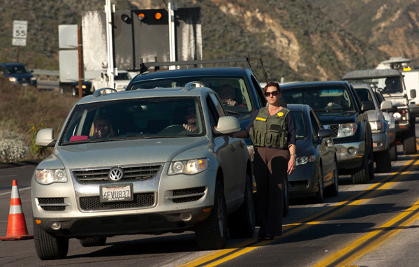 . ON13-MANHUNT-03-JCM (Jennifer Cappuccio Maher/Staff Photographer) Cars line up as San Bernardino County Sheriff\'s officials search vehicles heading down Highway 330 Tuesday, February 12, 2013, just above Highland. A man believed to be fired LAPD officer Christopher Dorner barricaded himself in a cabin in the San Bernardino Mountains.