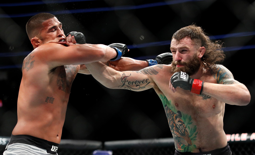 . Michael Chiesa hits Anthony Pettis during a lightweight mixed martial arts bout at UFC 226, Saturday, July 7, 2018, in Las Vegas. (AP Photo/John Locher)