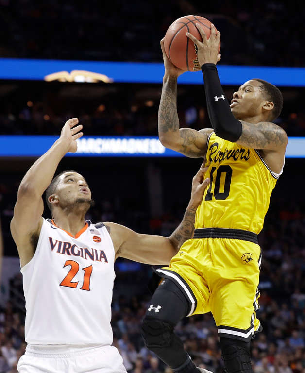 . UMBC\'s Jairus Lyles (10) shoots over Virginia\'s Isaiah Wilkins (21) during the second half of a first-round game in the NCAA men\'s college basketball tournament in Charlotte, N.C., Friday, March 16, 2018. (AP Photo/Gerry Broome)
