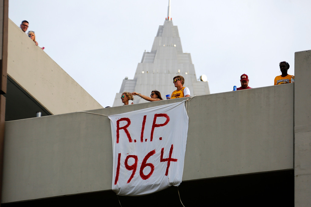 . Cleveland Cavalier fans hang a sign from a parking garage across from the Quicken Loans Arena early Wednesday, June 22, 2016, while waiting to watch a parade celebrating the Cleveland Cavaliers\' NBA Championship in downtown Cleveland .(AP Photo/Gene J. Puskar)