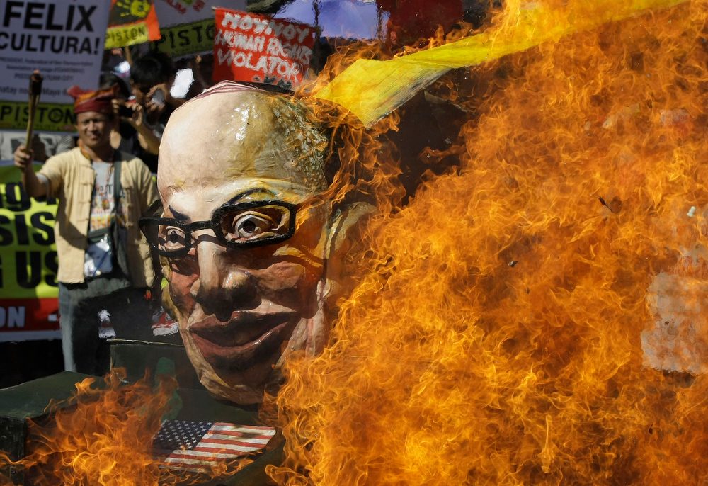 Description of . Protesters burn an effigy of Philippine President Benigno Aquino III on board a mock tank as they commemorate International Human Rights Day near the Presidential Palace in Manila, Philippines, on Monday Dec. 10, 2012. The group called the Aquino administration as alleged human rights violators. (AP Photo/Aaron Favila)